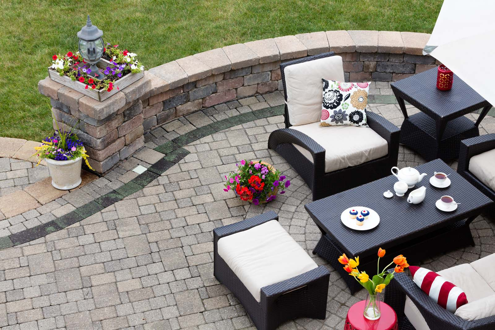 Brick paved patio with comfortable patio furniture with modern armchairs and a stool around a table set with tea and cookies alongside a low curving wall overlooking a green lawn high angle view