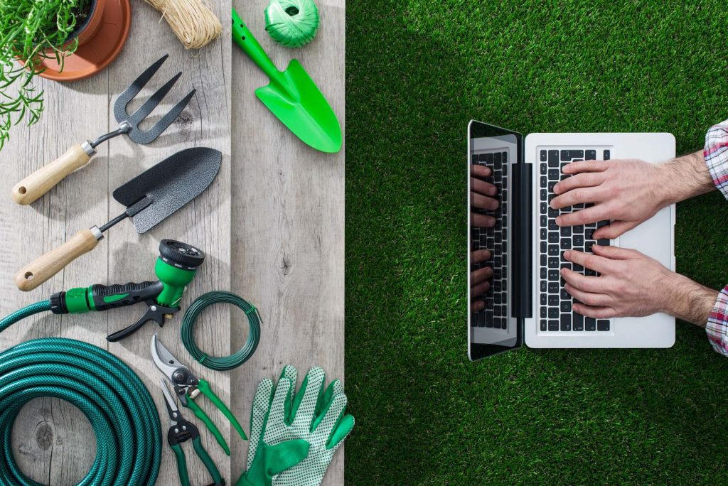 Gardening tools on a table and gardener networking with a laptop gardening and technology concept