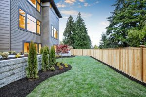 Luxurious contemporary three-story wood siding home exterior in Bellevue. Nice backyard landscape with well-kept lawn flower beds and wooden fence. Northwest USA