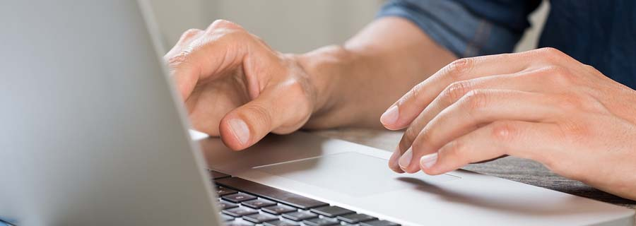 Closeup hand of businessman using laptop at office.